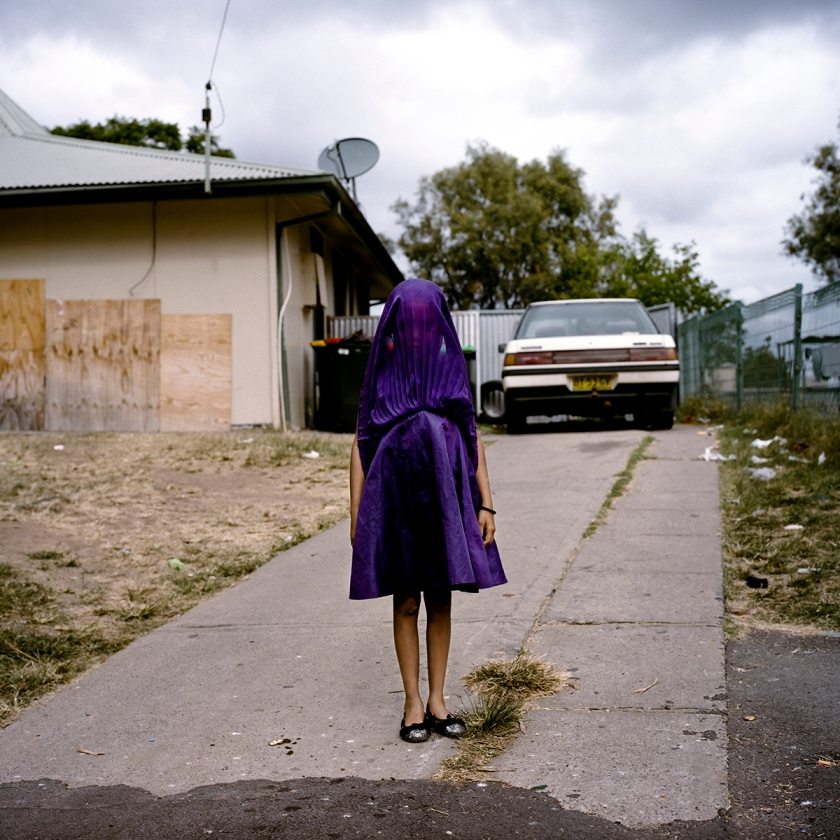 Laurinda waits in her purple dress for the bus that will take her to Sunday School.  Moree, New South Wales.