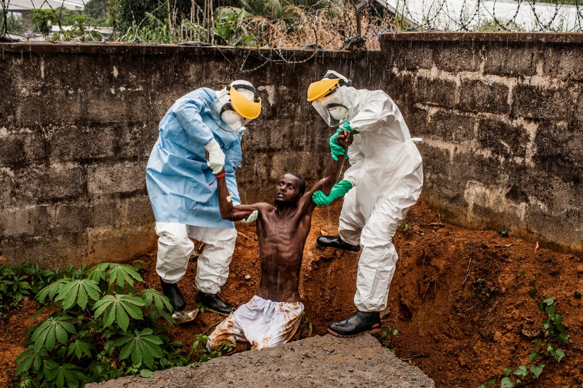 Medical staff at the Hastings Ebola Treatment Center work escort a man in the throes Ebola-induced delirium back into the isolation ward from which he escaped in Hastings, Sierra Leone on Sunday, November 23, 2014. In a state of confusion, he emerged from the isolation ward and attempted to escape over the back wall of the complex before collapsing in a convulsive state. A complete breakdown of metal facilities is a common stage of advanced Ebola. The man pictured here died shortly after this picture was taken.  (Pete Muller/Prime for National Geographic)