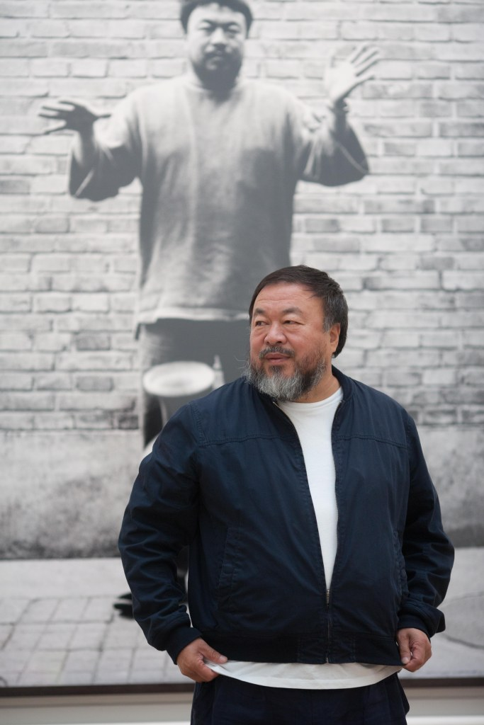Ai Weiwei with one of his photographs from Dropping a Han Dynasty Urn, Royal Academy of Arts, 2015. Ph. Dave Parry, Courtesy of Royal Academy of Arts, London.