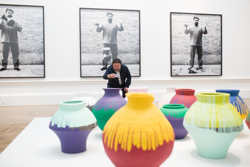 Ai Weiwei taking a photograph of his installation Coloured Vases, Royal Academy of Arts, 2015. Ph. Dave Parry, Courtesy of Royal Academy of Arts, London.